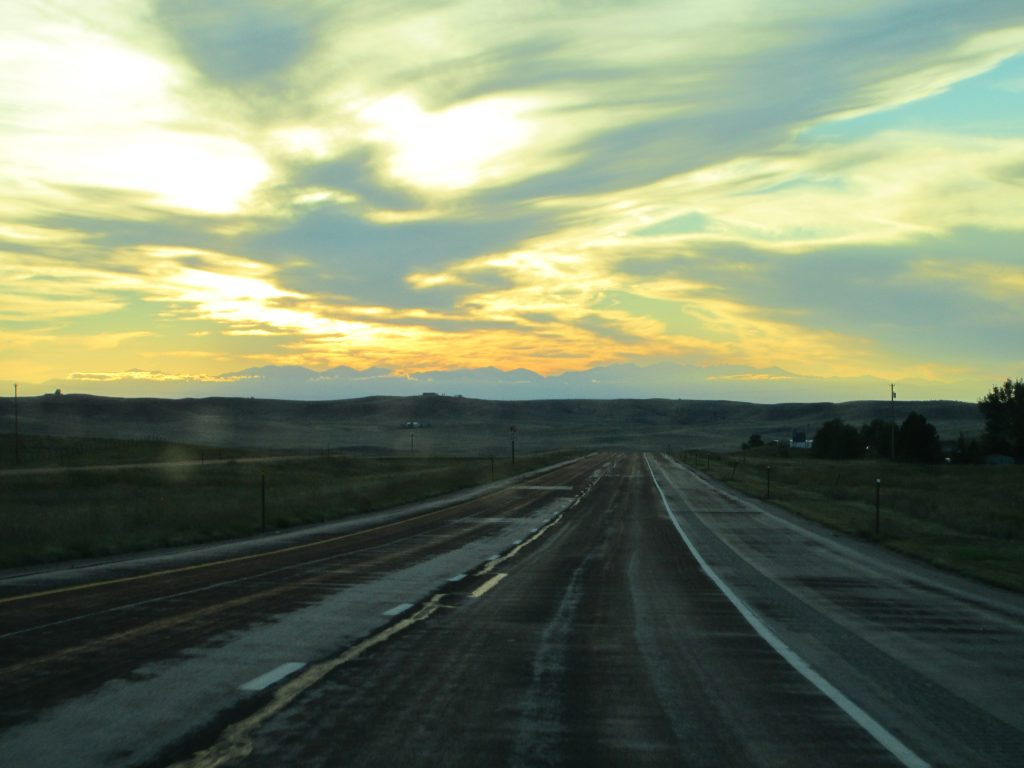 Empty road stretching into wide horizons and a distant sunset, representing the many possibilities of financial freedom.