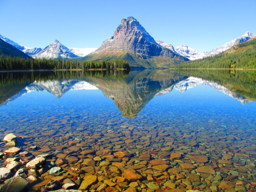 A mountain in the distance mirrored in a lake that is clear as glass. The photo illustrates the beauty, serenity, and peacefulness of the financially free lifestyle.