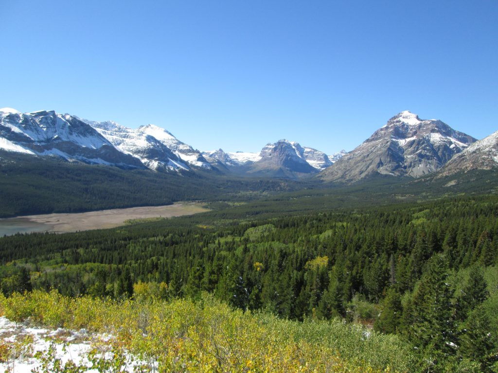 A green, sun-bathed valley surrounded in the distance by peaks of the Rocky Mountain range. An illustration of the rest and relaxation the author is enjoying through financial independence.