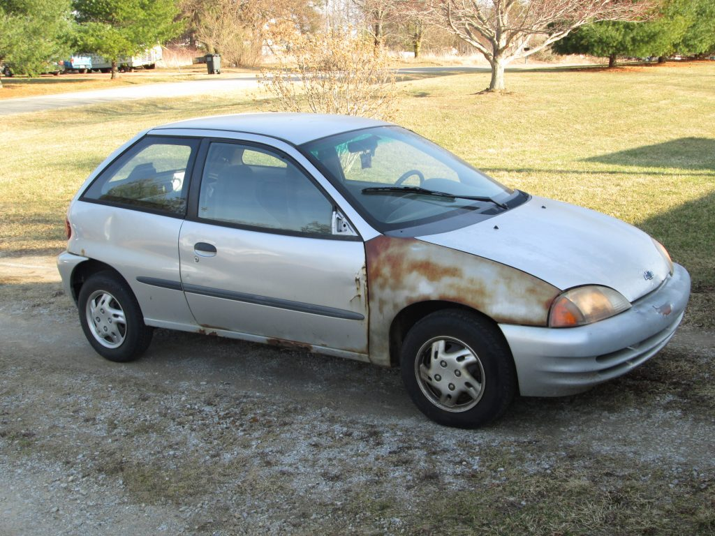 A beat-up silver Chevy Metro with no power steering, cruise control, or power options. Truly basic transportation illustrating the humble beginnings of the author and his wife at the time they were married.