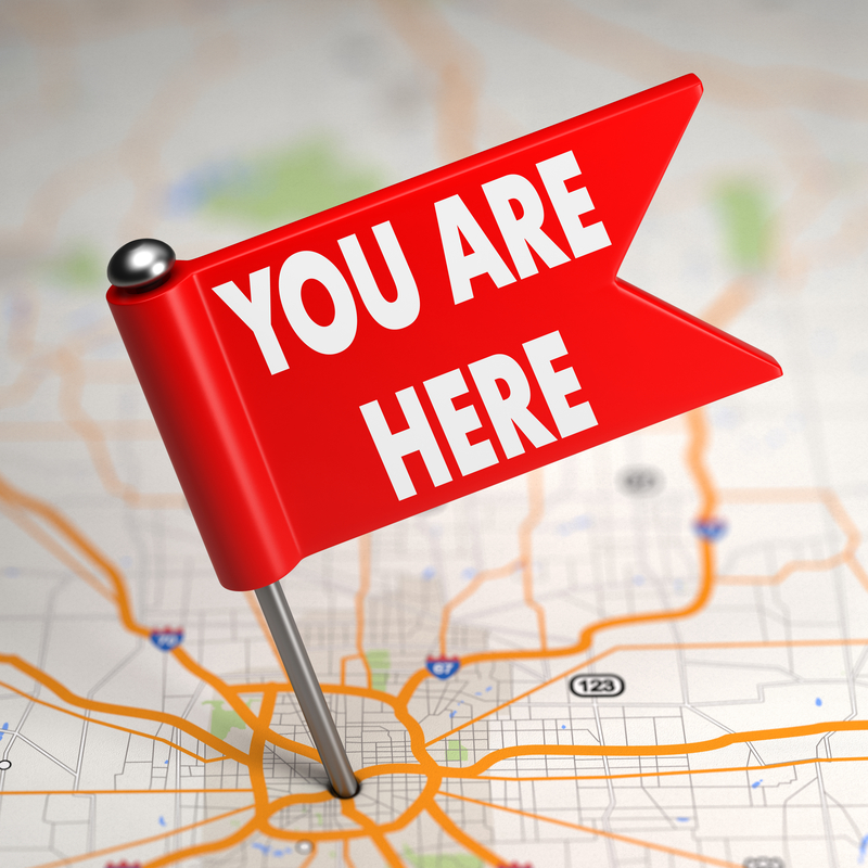 "A pin labeled ""You Are Here"" sticking into an atlas-style road map, illustrating the absolute necessity of identifying your financial starting point prior to charting a course to your financial goals."