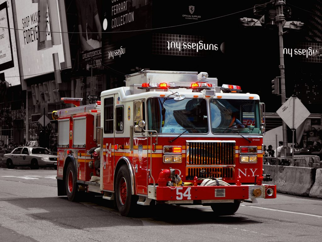 A NYC fire engine streaking down a street with lights ablaze, en route to a call. The photo illustrates how Mint is standing by to come to your bill pay rescue.