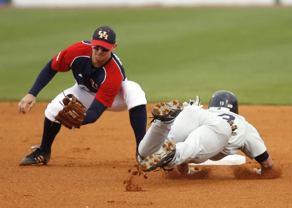 A baseball infielder making a play at the bag on a diving base-runner, illustrating the need to cover your budgeting bases in order to win with money.