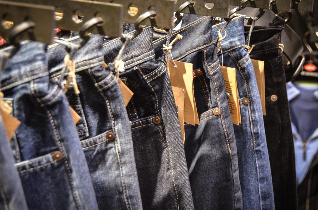 Jeans with price tags hanging on a retail clothes rack, illustrating the need to make a list of your savings goals and check the price tags on each.