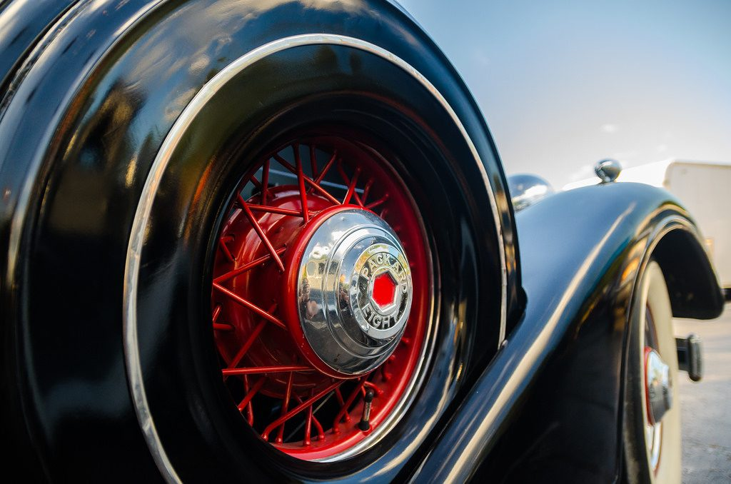 A close-up of a fender-mounted spare tire on a classic Packard roadster, illustrating the need to prepare for emergency on your financial freedom road trip.