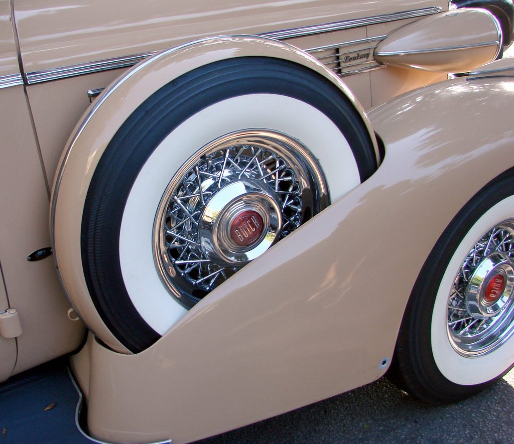 A close-up of a fender-mounted spare tire on a classic 1938 Buick, illustrating the need to pack your emergency fund spare tire.