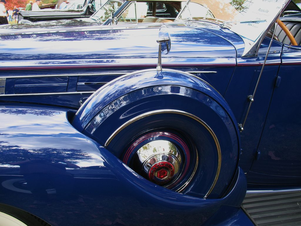 A close-up of a fender-mounted spare tire on a classic 1938 Packard, illustrating care necessary to store your emergency fund appropriately.