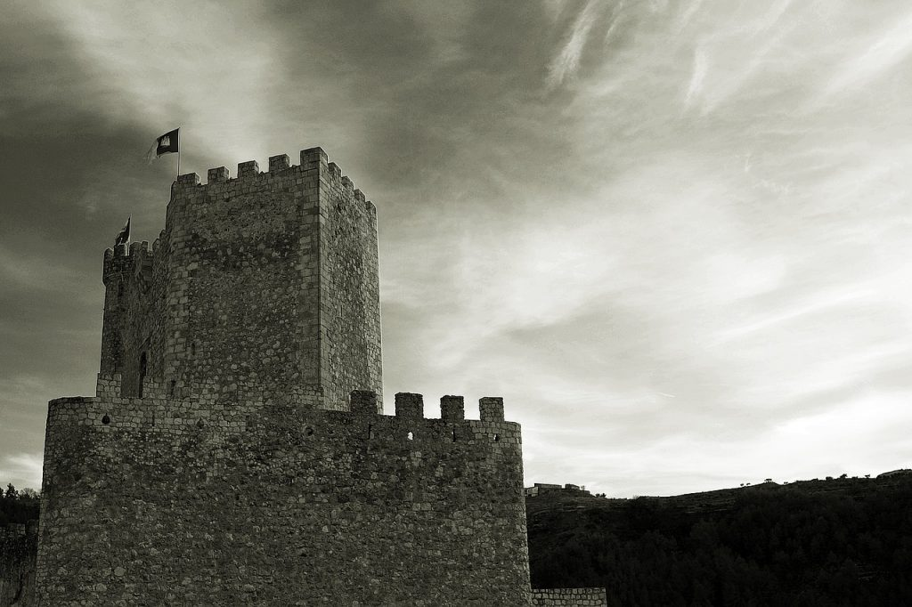 The battlements of a foreboding castle silhouetted against the sky, comparing the onerous bank fees charged by some institutions to the nefarious behavior of medieval robber barons.