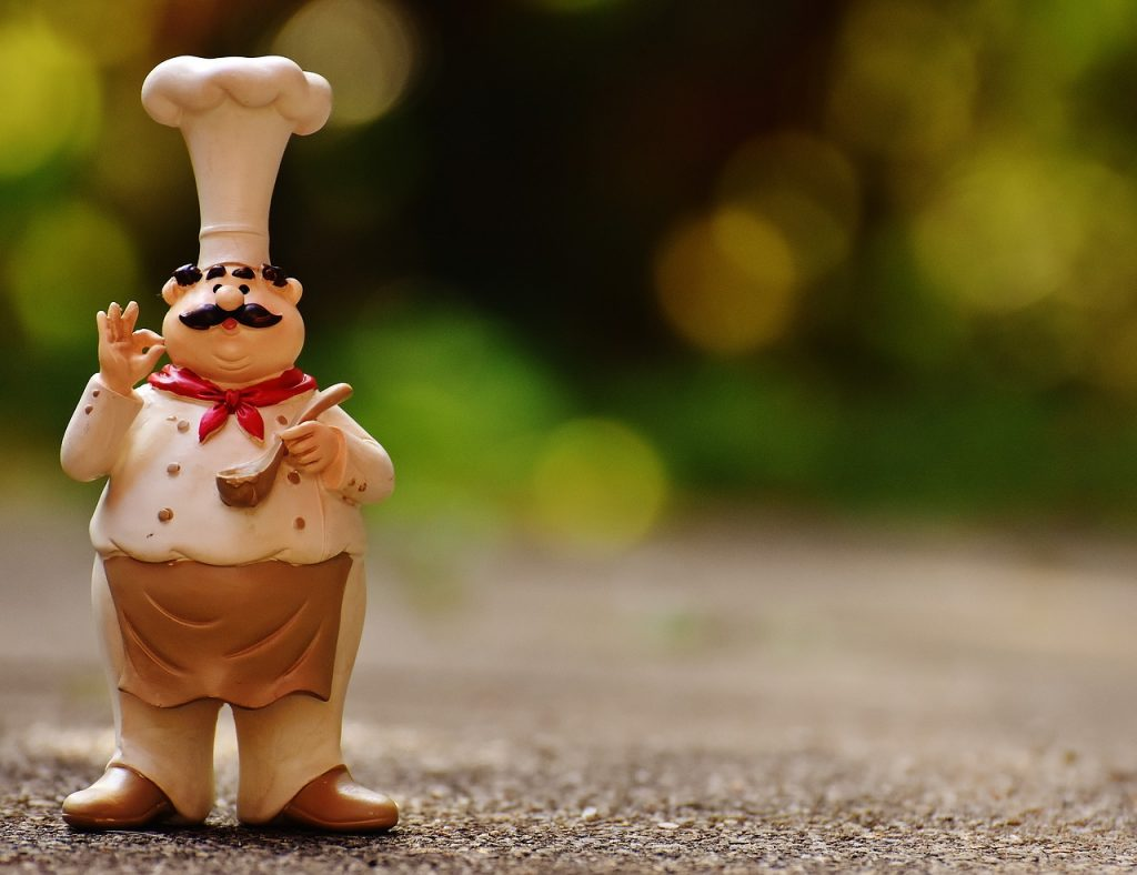 A chef figurine shown sampling sauce, illustrating how an automatic hidden bonus can serve as your secret budget sauce.