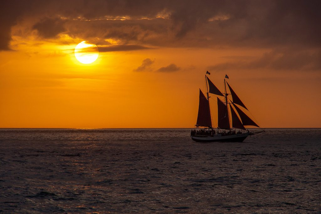 A sailboat cruising at sunset, illustrating the freeing power of automatic bill pay.