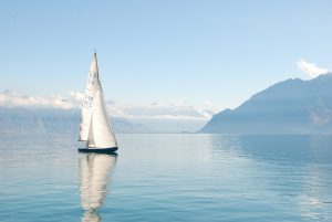A sailboat on a serene mountain lake, illustrating how automatic bill pay offers you the chance for leisure and a simplified life.