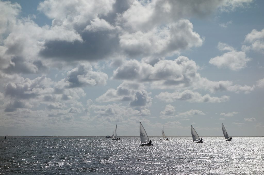 Five sailboats harnessing the power of the wind, illustrating how you can harness the five benefits of automatic bill pay.