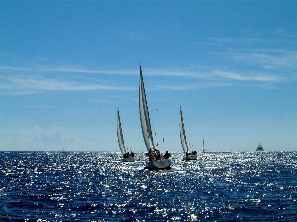 Three sailboats sailing together, illustrating the three unique risk/reward levels of automatic bill pay.