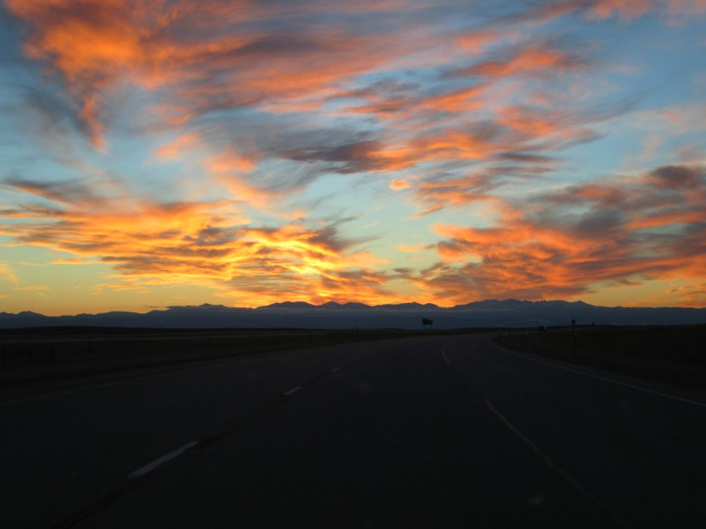Clouds in the sky painted orange, pink, and red by the sunset over the Bighorn Mountains.