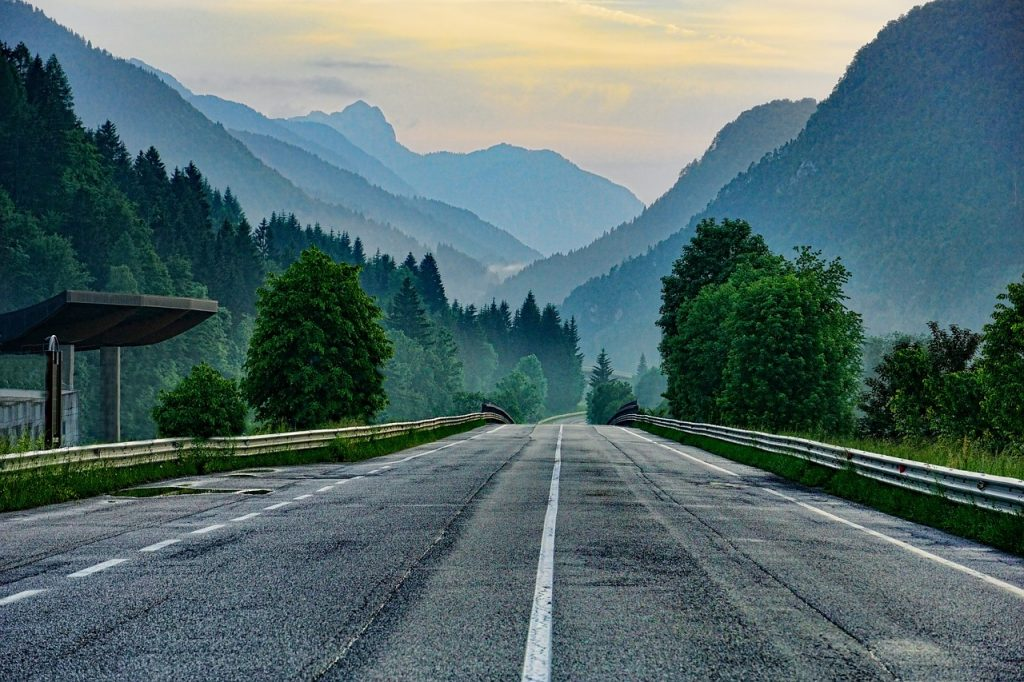 A road leading up into the mountains, illustrating the importance of facing your fears and climbing your money mountain to obtain financial freedom.