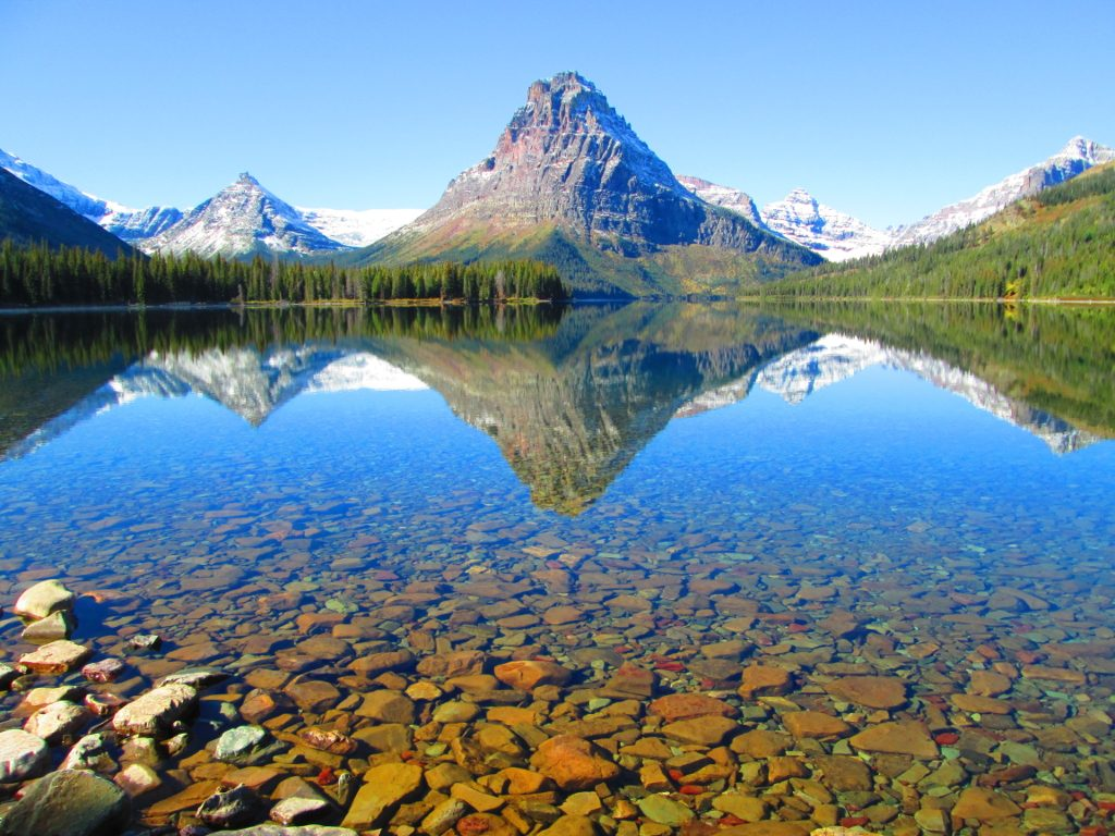 Dead-calm water on a lake in Glacier National Park, with a reflection of the Rockies silhoutted within it.