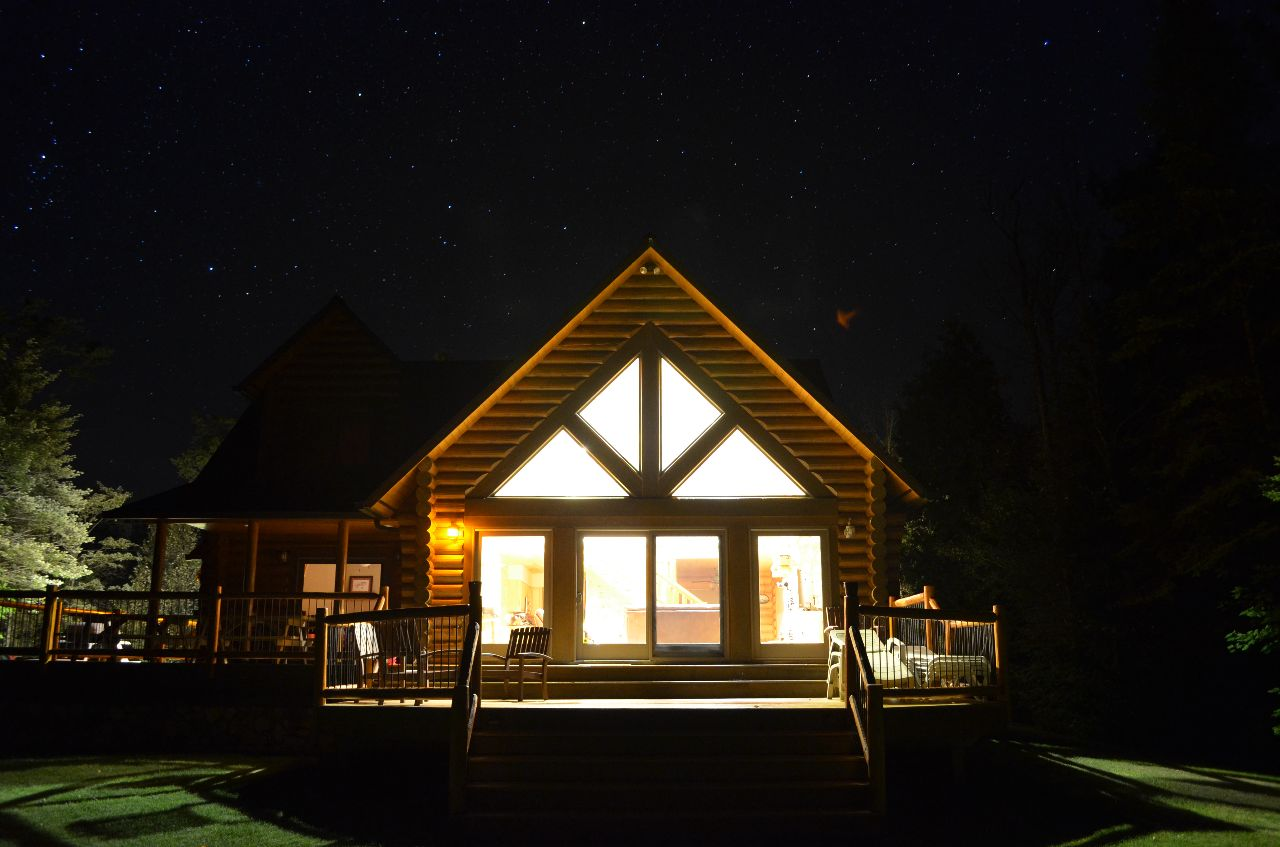 A well-lit cabin at night in Michigan's Upper Peninsula, surrounded by a backdrop of starry skies.